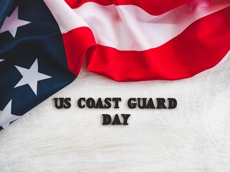 Belle carte pour la journée des garde-côtes américains. Lettres en bois avec une inscription de félicitations sur fond blanc. Gros plan, vue de dessus. Félicitations aux proches, parents, amis et collègues