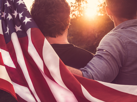 Two friends hold American Flag at sunset Imagens