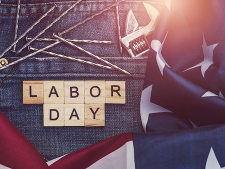 LABOR DAY. American Flag, wrench, nails, stylish jeans and wooden letters of the alphabet. Top view, close-up. Preparations for celebration. Congratulations for relatives, friends and colleagues