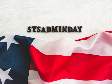 Beautiful greeting card for Sysadmin Day. Wooden letters with a congratulatory inscription on a white background. Close-up, top view. Congratulations for loved ones, friends and colleagues Reklamní fotografie