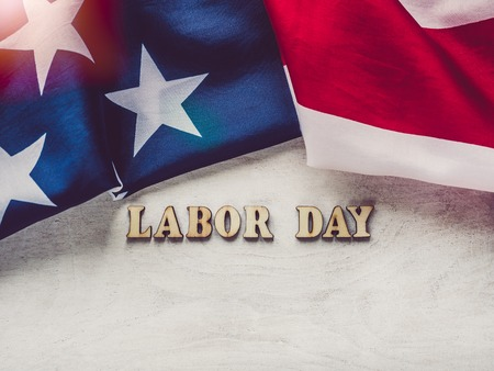 LABOR DAY. American flag and wooden letters of the alphabet on a white table. Close-up, top view. Bright photo with space for your inscriptions. Congratulations to relatives, friends and colleagues