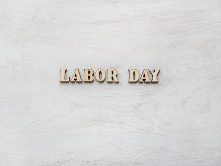 Wooden letters with a congratulatory inscription LABOR DAY. Close-up, top view, isolated. Concept of preparing for the holiday. Congratulations for loved ones, relatives, friends, colleagues
