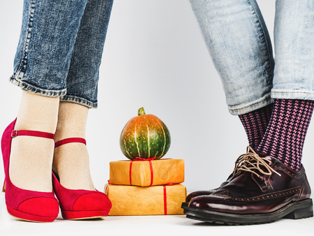 Men's and women's legs in fashionable shoes, colorful, multi-colored socks on a white, isolated background. Close-up. Concept of Style, Fashion and Beauty