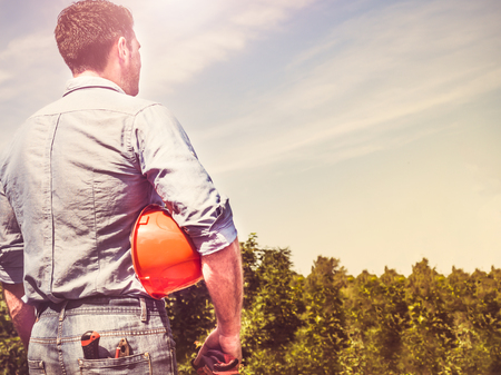 Attractive man with tools, standing against a background of green trees and the rays of the setting sun. View from the back, close-up. Concept of work and employment Stock Photo