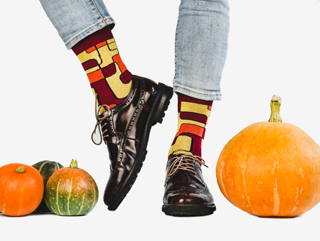 Men's legs, fashionable shoes, colorful, multi-colored socks on a white, isolated background. Close-up. Concept of Style, Fashion and Beauty