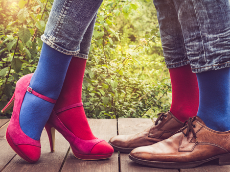 Men's and women's legs in fashionable shoes, bright, multi-colored socks on a wooden terrace on the background of green trees and sunlight. Close-up. Concept of Style, Fashion and Beauty Archivio Fotografico