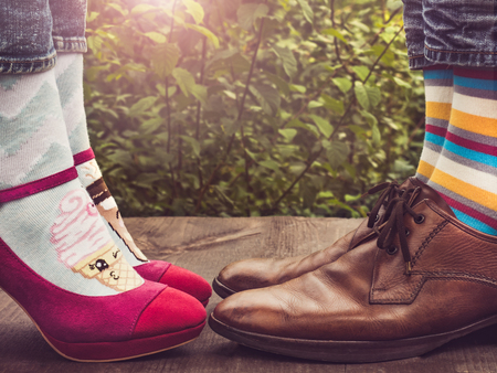 Men's and women's legs in fashionable shoes, bright, multi-colored socks on a wooden terrace on the background of green trees and sunlight. Close-up. Concept of Style, Fashion and Beauty