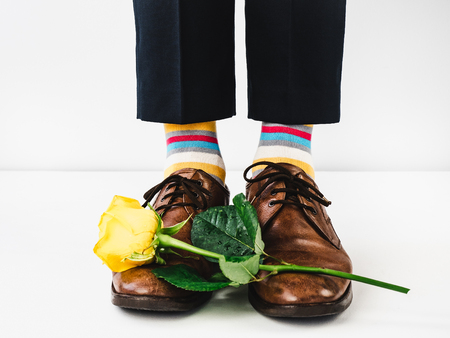 Office manager standing in stylish shoes, black pants and bright, colorful socks on a white, isolated background. Close-up. Studio photo. Concept of lifestyle, fun and elegance