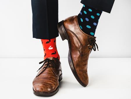 Responsabile dell'ufficio in piedi con scarpe eleganti, pantaloni blu e calzini luminosi e colorati su uno sfondo bianco e isolato. Avvicinamento. Foto da studio. Concetto di lifestyle, divertimento ed eleganza