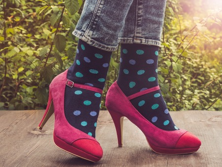 Womens legs in fashionable shoes, bright, multi-colored socks on a wooden terrace on the background of green trees and sunny rays. Close-up. Concept of Style, Fashion and Beauty