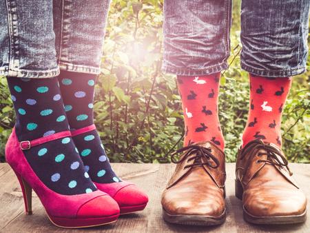 Männer- und Frauenbeine in modischen Schuhen, helle, mehrfarbige Socken auf einer Holzterrasse vor dem Hintergrund grüner Bäume und sonniger Strahlen. Nahaufnahme. Konzept von Stil, Mode und Schönheit