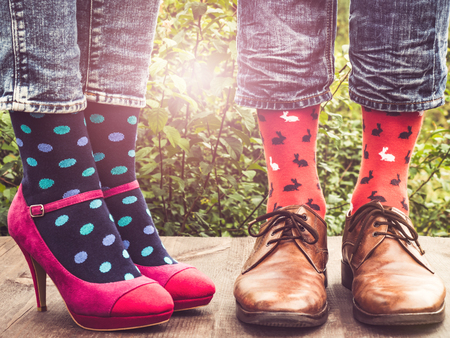 Mens and womens legs in fashionable shoes, bright, multi-colored socks on a wooden terrace on the background of green trees and sunny rays. Close-up. Concept of Style, Fashion and Beauty