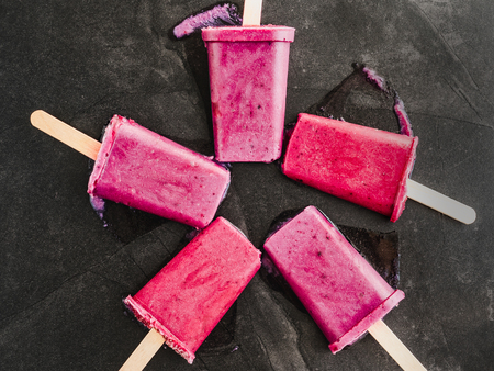 Bright, fruity fuchsia ice cream with wooden sticks on a dark surface. Close-up, top view. Tasty and healthy food concept