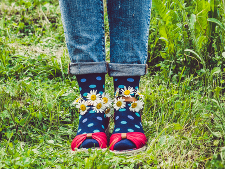 Womens legs, fashionable shoes, bright multi-colored socks on a background of green grass. Close-up. Concept of style, fashion and beauty Banco de Imagens