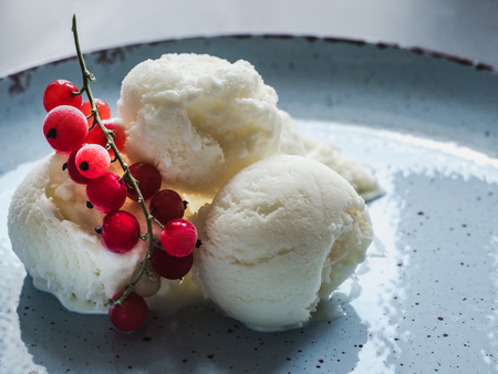 Bright, flavor ice cream and a sprig of red currants. Isolated background. Close-up, top view. Concept of tasty and healthy food