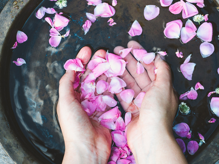 Hands of a young woman, bright petals of roses and old, copper basins with water. Top view, close-up. Beauty and body care concept
