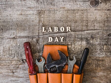 LABOR DAY. Hand tools and wooden letters lying on the desk. Top view, close-up. Preparing for the celebration. Congratulations to family,relatives, friends, colleagues. Concept of labor and employment
