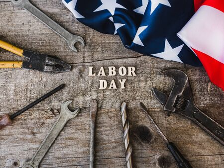LABOR DAY. Hand tools, American Flag and wooden letters lying on the desk. Top view, close-up. Congratulations to family, relatives, friends, colleagues. Concept of labor and employment Reklamní fotografie - 125859946