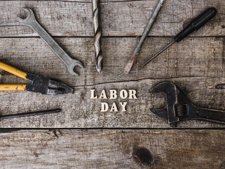 LABOR DAY. Hand tools and wooden letters lying on the table. Top view, close-up. Preparing for the celebration. Congratulations to loved ones, family, relatives, friends and colleagues Reklamní fotografie