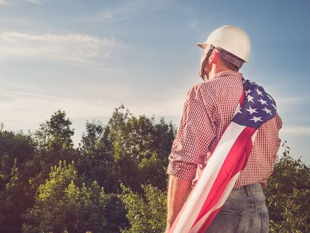 Young engineer in a white helmet, holding an American Flag in the park against the backdrop of green trees and the setting sun, looking into the distance. Close-up. Concept of labor and employment Reklamní fotografie - 125859986