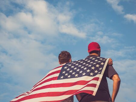 Two attractive guys holding an American Flag against a clear, sunny, blue sky. View from the back. Preparing for the holidays Reklamní fotografie - 125859994