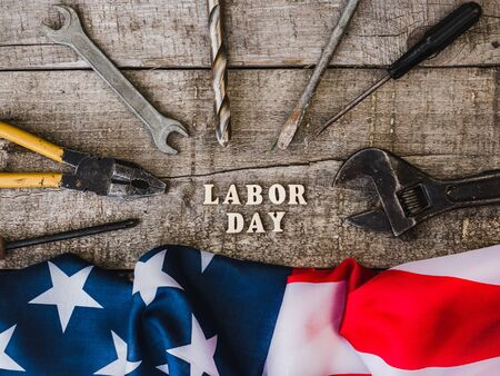 LABOR DAY. Hand tools, American Flag and wooden letters lying on the desk. Top view, close-up. Congratulations to family, relatives, friends, colleagues. Concept of labor and employment Reklamní fotografie - 125860023