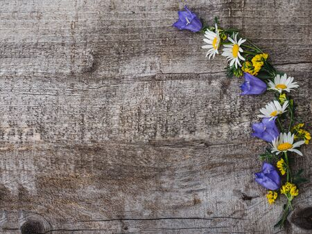 Beautiful, bright wildflowers lying on unpainted desk. Place for your inscription. Top view, close-up. Congratulations to loved ones, family, relatives, friends and colleagues Reklamní fotografie - 125860041