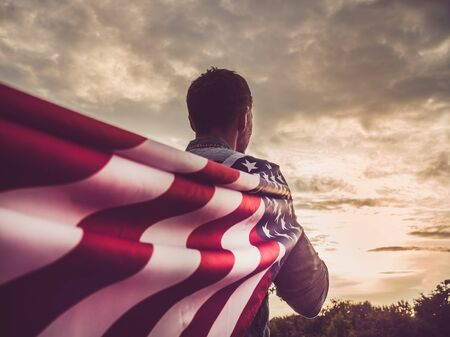 Attractive man in jeans and a denim shirt waving an American flag against the backdrop of a sunset and a gray, gloomy sky. View from the back, close-up. National holiday concept Reklamní fotografie - 126378131