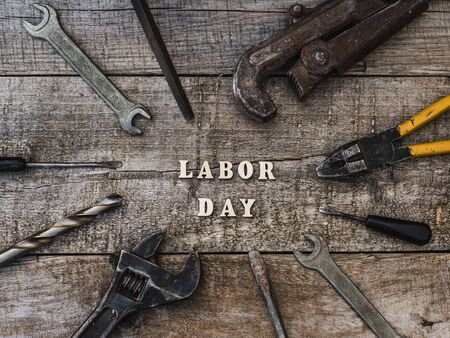 LABOR DAY. Hand tools and wooden letters lying on the table. Top view, close-up. Preparing for the celebration. Congratulations to loved ones, family, relatives, friends and colleagues Reklamní fotografie - 126378299