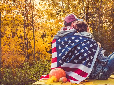 Happy married couple holding the US flag against the background of yellow trees and the setting sun. Happy relationship concept Reklamní fotografie - 127073004