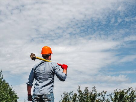 Attractive man holding a hammer in the park
