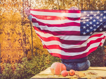 Attractive guy holding a US flag against the background of yellow trees and the setting sun. National holiday concept