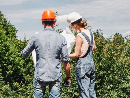 Young engineer woman and her subordinate worker holding a paper project in the park against the backdrop of green trees. Close-up. Concept of labor and employment Reklamní fotografie
