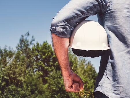 Handsome engineer, holding white hardhat in the park against the backdrop of green trees and the setting sun, looking into the distance. Close-up. Concept of labor and employment