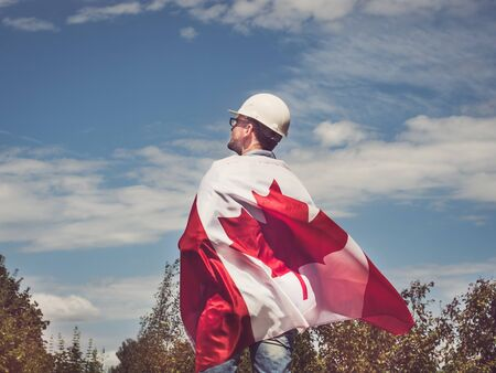 Engineer, holding Canadian Flag in the park