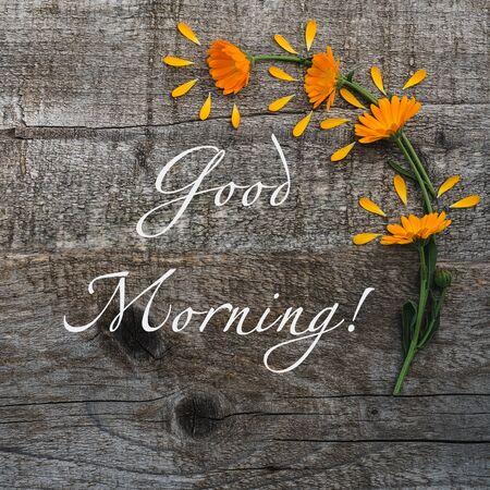 Hermosas flores brillantes sobre tableros sin pintar e inscripción manuscrita BUENOS DÍAS. Vista superior, primer plano. Felicitaciones a seres queridos, familiares, parientes, amigos y colegas. Foto de archivo