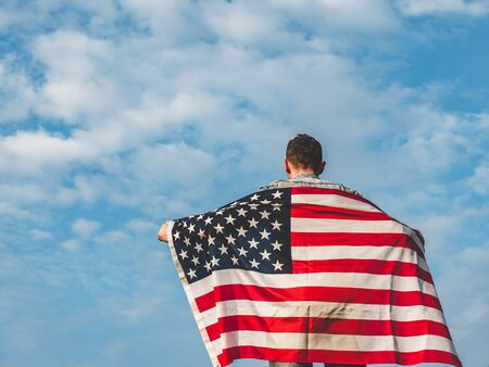 Attractive man in jeans and denim shirt waving an American Flag against a clear, sunny, blue sky. View from the back, close-up. National holiday concept