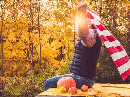 Attractive guy holding a US flag against the background of yellow trees and the setting sun. National holiday concept. Close-up, outdoors