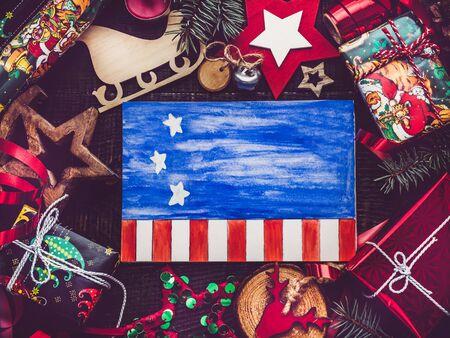 メリークリスマスと明けましておめでとうございます。アメリカ国旗パターンの美しいカード。上からの眺め、クローズアップ、フラットレイ。愛する人、家族、親戚、友人、同僚におめでとうございます