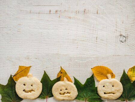 Happy Halloween. Fragrant, fresh cookies in the shape of a pumpkin, yellow and green leaves, lying on a white board. Top view, close-up. Congratulations to loved ones, relatives, friends, colleagues
