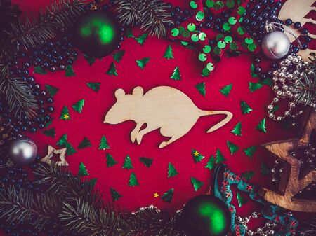 Wooden figure of a rat and Christmas decorations. View from above, close-up, flat lay. Congratulations to loved ones, family, relatives, friends and colleagues