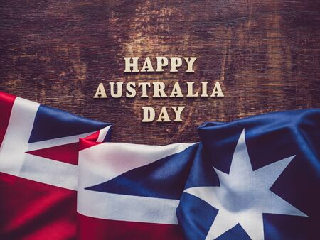 Wooden unpainted letters of the alphabet on a dark background. Australia Day. Beautiful, bright card. Top view, close-up. National holiday concept