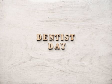 Dentist's day greeting card. White, isolated background, close-up, view from above, wooden surface. Congratulations for relatives, friends and colleagues