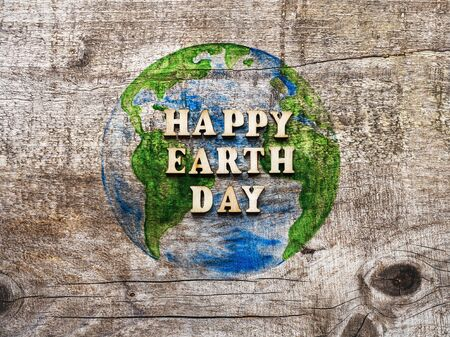 Earth Day. Beautiful greeting card. Isolated background, close-up, view from above, wooden surface. Congratulations for relatives, friends and colleagues