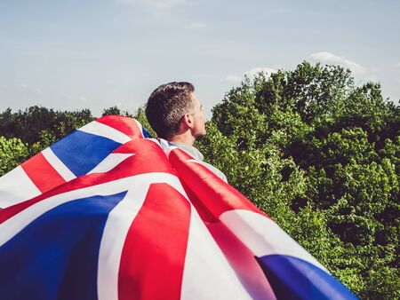 Attractive man holding Australian Flag on blue sky background on a clear, sunny day. View from the back, close-up. National holiday concept
