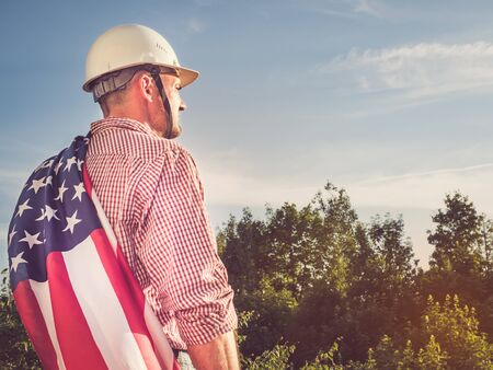 Young engineer, white hardhat and an American Flag in the park against the backdrop of green trees and the setting sun, looking into the distance. Close-up. Concept of labor and employment