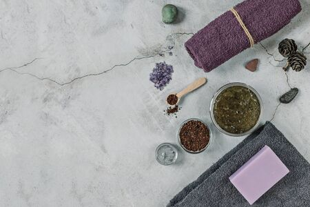 On a gray background are accessories for Spa self-care: body scrub, ground coffee, lavender soap, face mask cream,bath salt ,Terry towels for face and body.