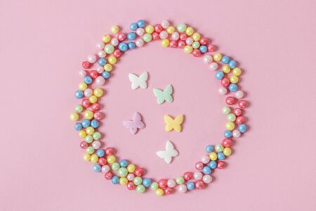 Pastry sprinkles are scattered in the form of a circle, inside it are enclosed colorful butterflies on a pink background. Foto de archivo