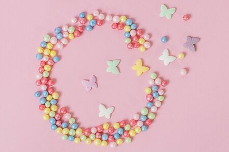 Pastry sprinkles are scattered in the form of a ragged circle, with multicolored butterflies flying out of it on a pink background.