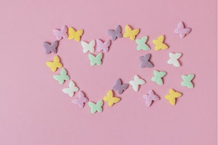 Pastry multicolored sprinkles-butterflies are laid out in the form of a decaying heart on a pink background. Decoration of confectionery products